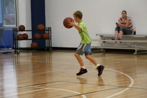 Young Boy Dribbling on the Basketball Court at The HUB Recreation Center