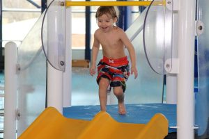 Young Boy Smiling Down the Slide at The HUB Recreation Center in Marion Illinois