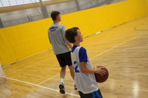 Young Boy Playing Basketball at The HUB Recreation Center Pictured with Coach