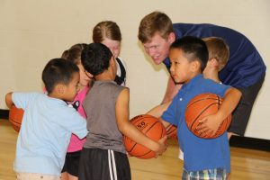 Kids and Coach Reaching Hands in at The HUB Recreation Center in Marion Illinois