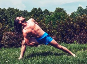 Fit Young Man with Long Hair Holding Yoga Pose in the Grass