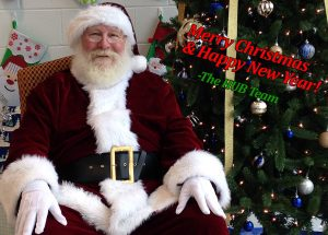 Santa Claus in front of a Christmas tree and stockings at The HUB Recreation Center