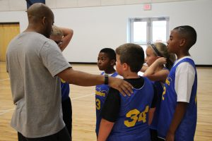 Young Boys and Girls Hudding with Basketball Coach at The HUB Recreation Center