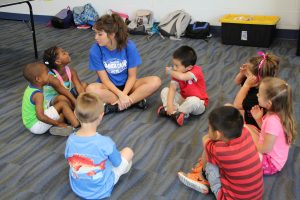 Small Boys and Girls Sitting in a Circle with Camp Counselor at The HUB Recreation Center