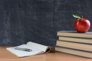 closeup of a teachers desk with books, paper and pen and a red apple in front of a chalkboard