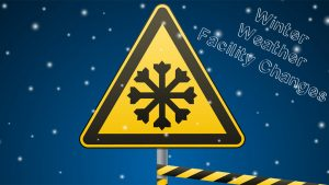 Yellow Street Sign with Snowflake in Front of Snowy Blue and White Background