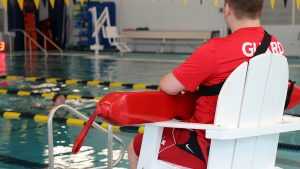 Lifeguard in Chair Watching Over Swimmer