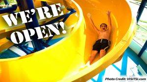 Boy Going Down the Waterslide with Arms in the Air