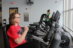 Woman on indoor cycle bike at fitness center